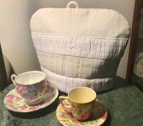 Linen Cozy w/Antigue Trim, sitting behind two Chintz cups & saucers.